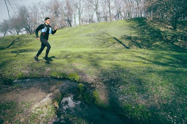 Homem correndo em um parque ou floresta contra o espaço das árvores