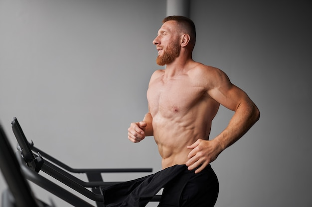 Homem correndo na esteira de ginástica
