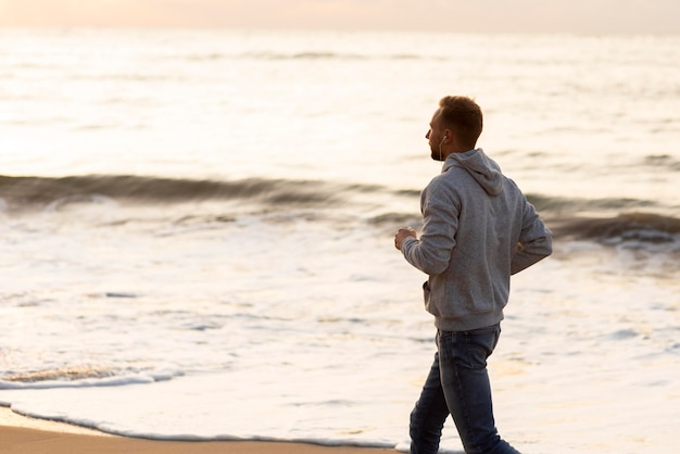 Homem correndo na praia com espaço de cópia