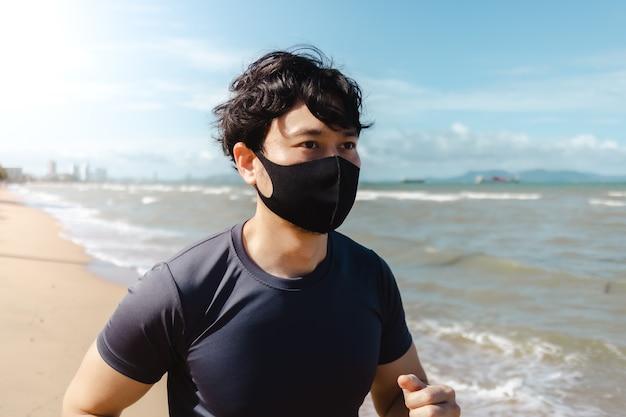 Homem correndo na praia com máscara na manhã de verão