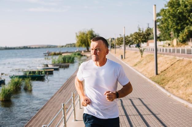 Homem correndo pelo lago tiro médio