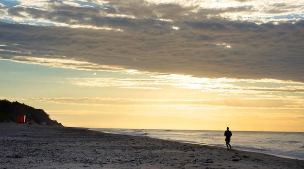 Homem correndo sozinho na praia ao nascer do sol