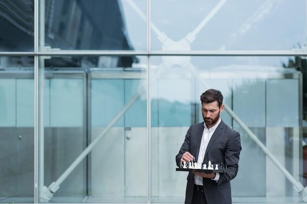 Homem corretor de negócios em pé perto do escritório, segurando uma prancha jogando xadrez, pensando sobre a estratégia de negócios