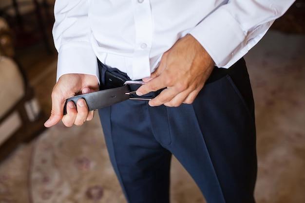 Homem corrige cinto, taxas noivo, mãos do homem, vestir-se, homem botões calças, jeans
