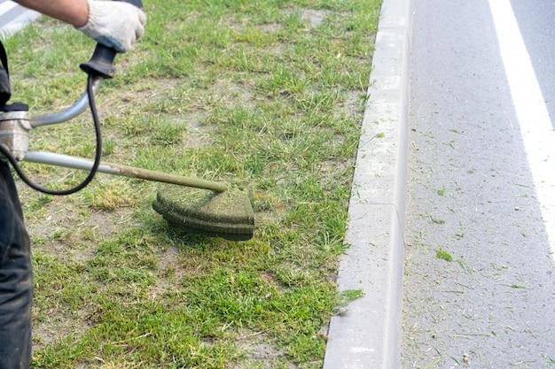 Homem corta a grama com um cortador de grama