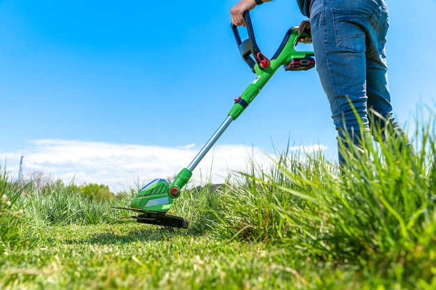 Homem corta a grama no prado com um cortador de grama portátil sem fio