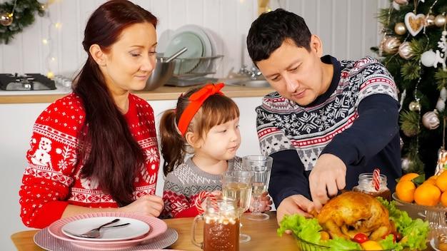 Homem corta frango para alimentar a família sentada à mesa do feriado