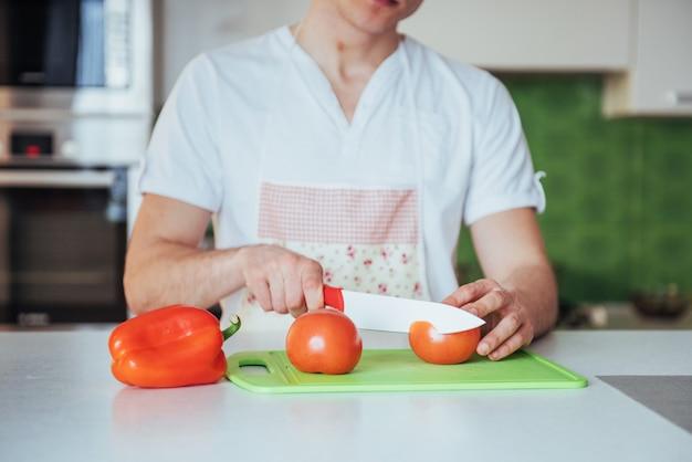 Homem corta legumes juntos na cozinha