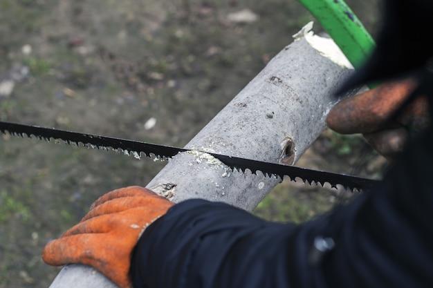 Homem corta madeira com uma serra manual