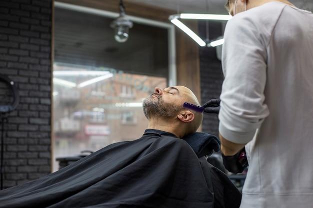 Homem cortando a barba na barbearia.