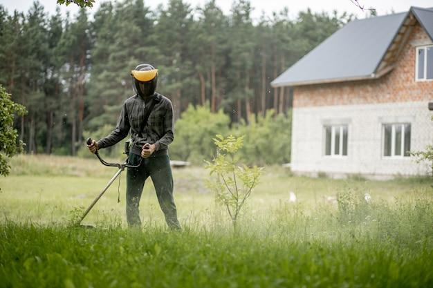 Homem cortando a grama em seu jardim. jardineiro cortando a grama. estilo de vida.