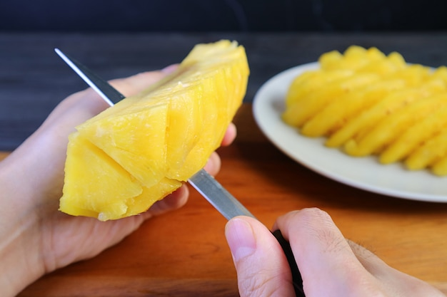 Homem cortando abacaxi maduro fresco em pedaços antes de servir