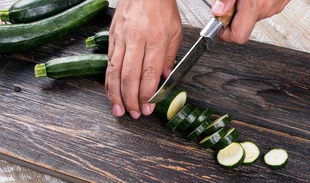Homem cortando abobrinhas frescas em fatias sobre uma tábua sobre uma mesa de madeira