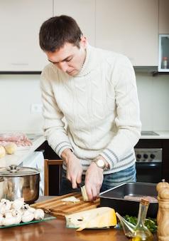 Homem cortando batata na cozinha