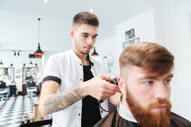 Homem cortando cabelo com tesoura na barbearia