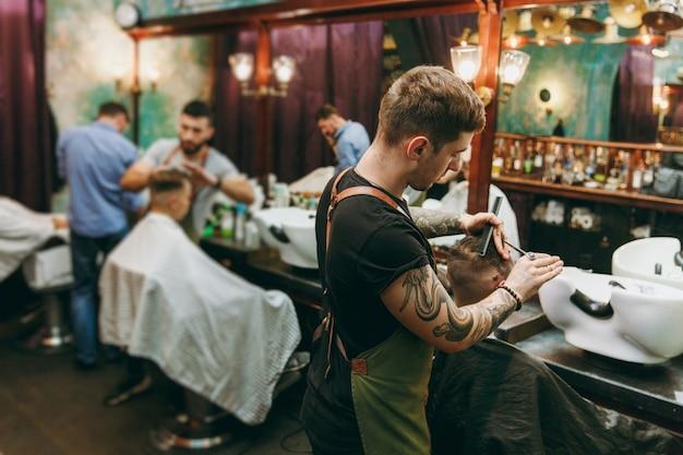 Homem cortando cabelo da moda na barbearia. o cabeleireiro masculino em tatuagens atendendo o cliente.