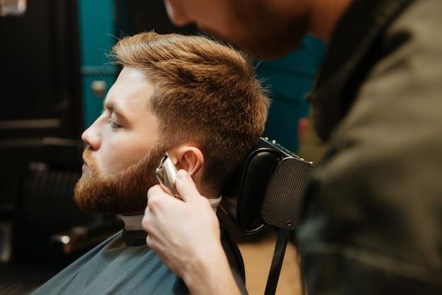 Homem cortando cabelo de barba por cabeleireiro enquanto está sentado na cadeira de barbearia.