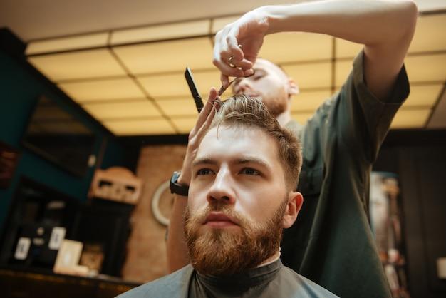 Homem cortando cabelo de cabeleireiro com uma tesoura enquanto está sentado na cadeira.