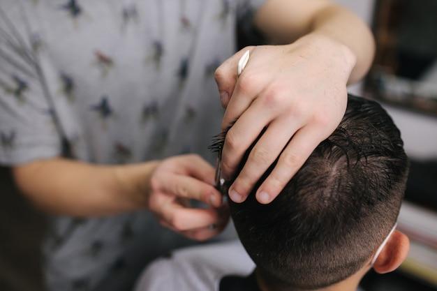 Homem cortando cabelo na barbearia usando máscara durante a pandemia de coronavírus. barbeiro profissional usando luvas. covid-19, conceito de beleza, autocuidado, estilo, saúde e medicina.