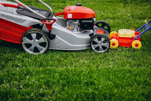 Homem cortando grama com motor de gramado no quintal