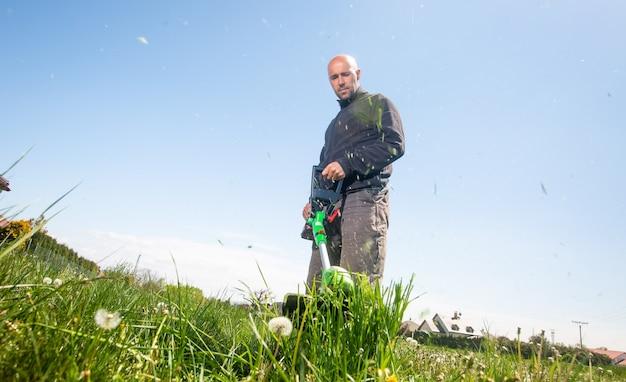 Homem cortando grama, cortando grama em seu enorme jardim, campo verde perto do cortador de jardim motorizado, conceito de jardinagem