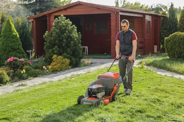 Homem cortando grama no quintal