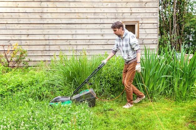 Homem cortando grama verde com cortador de grama no quintal. fundo de estilo de vida rural de jardinagem