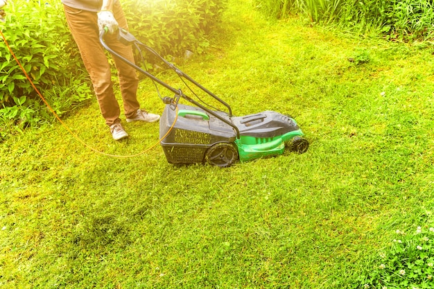Homem cortando grama verde com cortador de grama no quintal