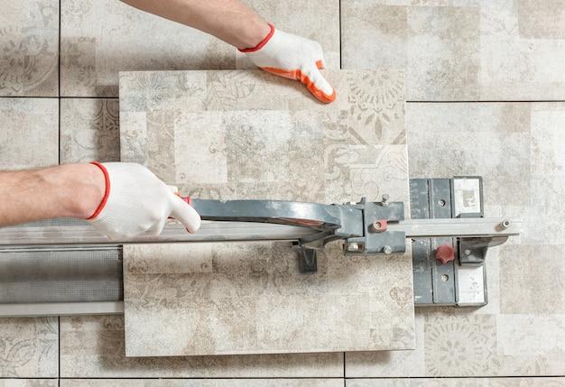Homem cortando ladrilho de cerâmica com um cortador de ladrilhos