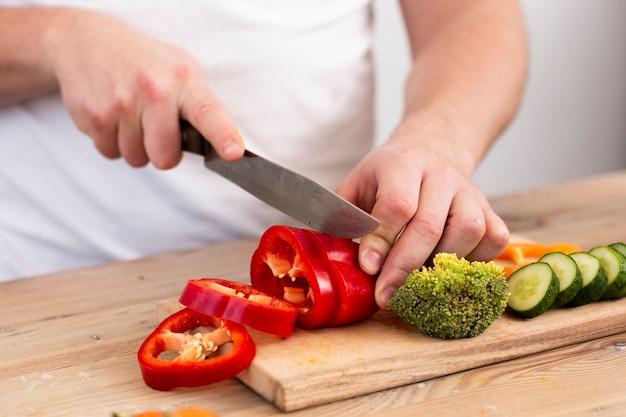 Homem cortando legumes em uma bandeja de madeira