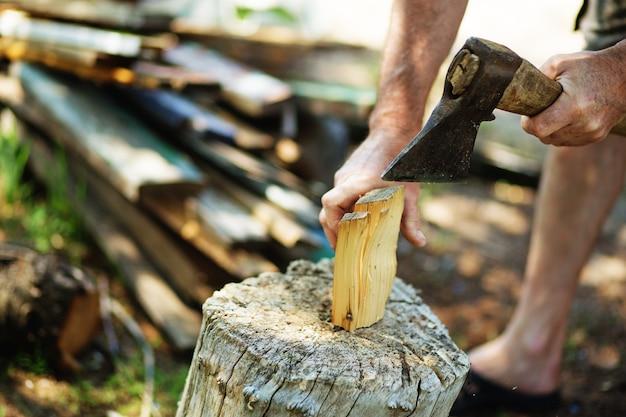 Homem cortando lenha com machado vintage