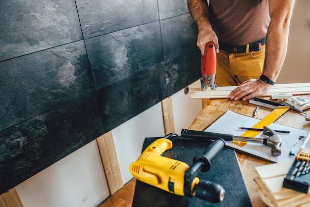 Homem cortando madeira com serra elétrica