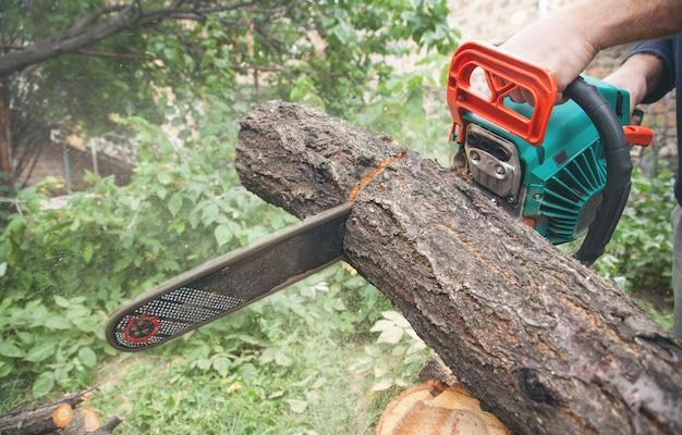 Homem cortando madeira com uma serra elétrica.
