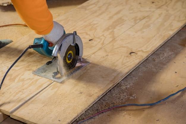 Homem cortando madeira compensada usando uma motosserra elétrica, ferramentas profissionais