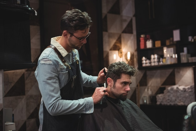 Homem cortando o cabelo com navalha