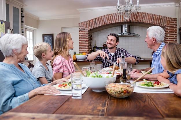 Homem cortando peru assado ao fazer uma refeição com sua família