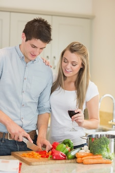 Homem cortando pimentas com mulher bebendo vinho Foto Premium