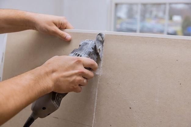 Homem cortando placa de drywall de gesso usando ferramentas elétricas angulares manuais