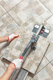 Homem cortando uma placa de cerâmica com um cortador de azulejos