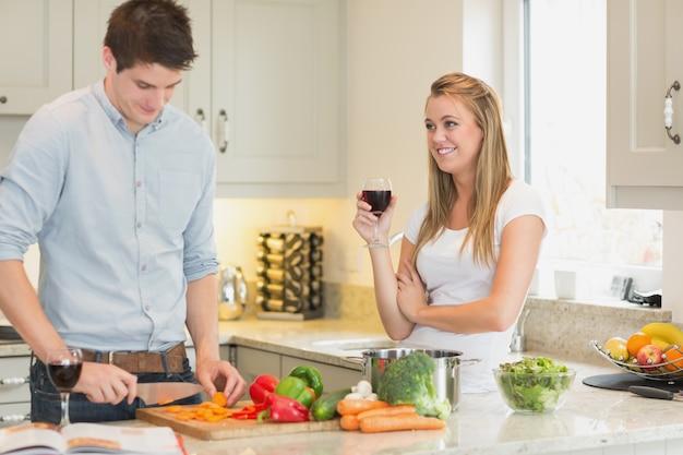 Homem cortando vegetais com mulher bebendo vinho Foto Premium