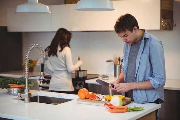 Homem cortando vegetais na cozinha enquanto a mulher cozinhando comida no fundo