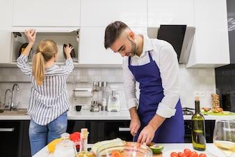 Homem, corte, legumes, enquanto, mulher, levando, pratos