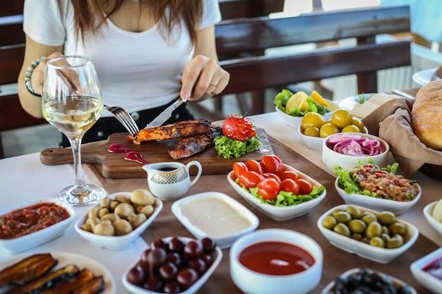 Homem, corte, truta grelhada, azeitonas, tomate, mangal, salada, berinjelas, vista lateral