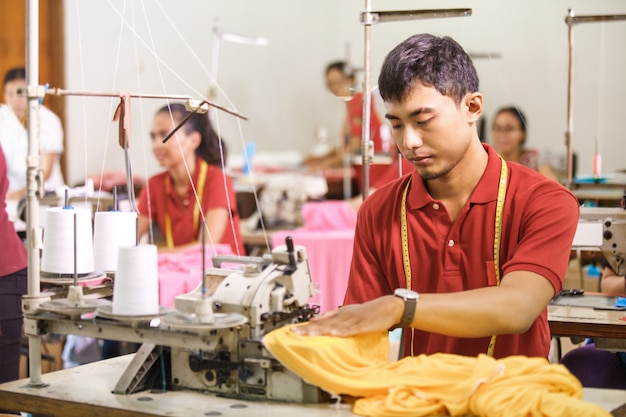 Homem costurando em um sewinghine em uma fábrica de roupas