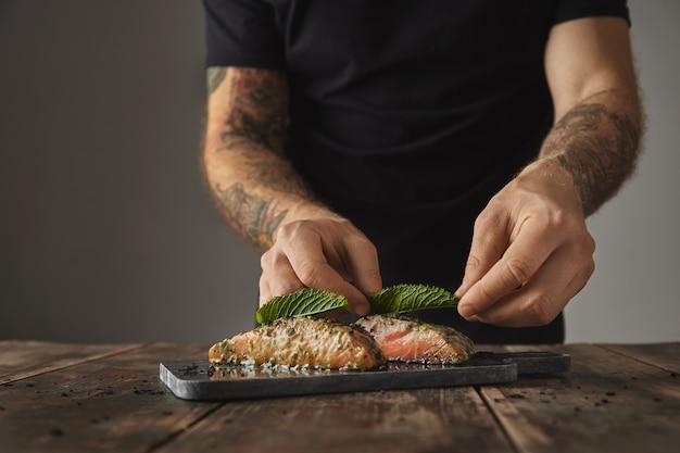 Homem cozinha refeição saudável em mesa rústica, decore com folha de hortelã dois pedaços crus de salmão em molho de vinho branco com especiarias e ervas apresentadas no deque de mármore preparado para grelhar