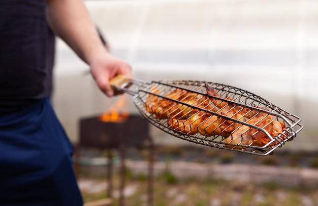 Homem cozinhando carne no churrasco. diversão no verão.