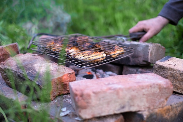 Homem cozinhando churrasco de carne na grelha em seu jardim em tijolos simples