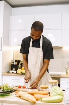 Homem cozinhando. homem afro-americano em uma cozinha. homem de camiseta preta.