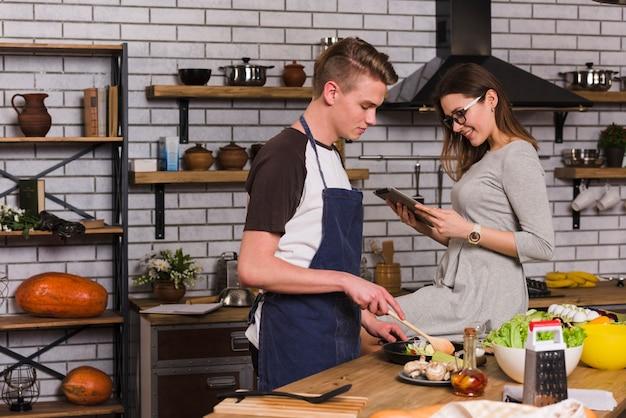 Homem, cozinhando jantar, com, mulher senta-se, perto