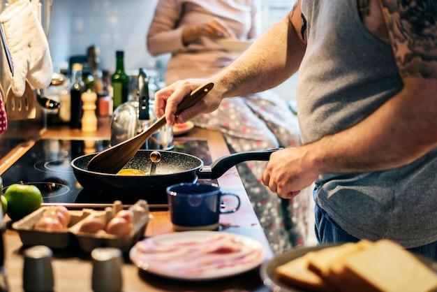 Homem cozinhando o café da manhã na cozinha